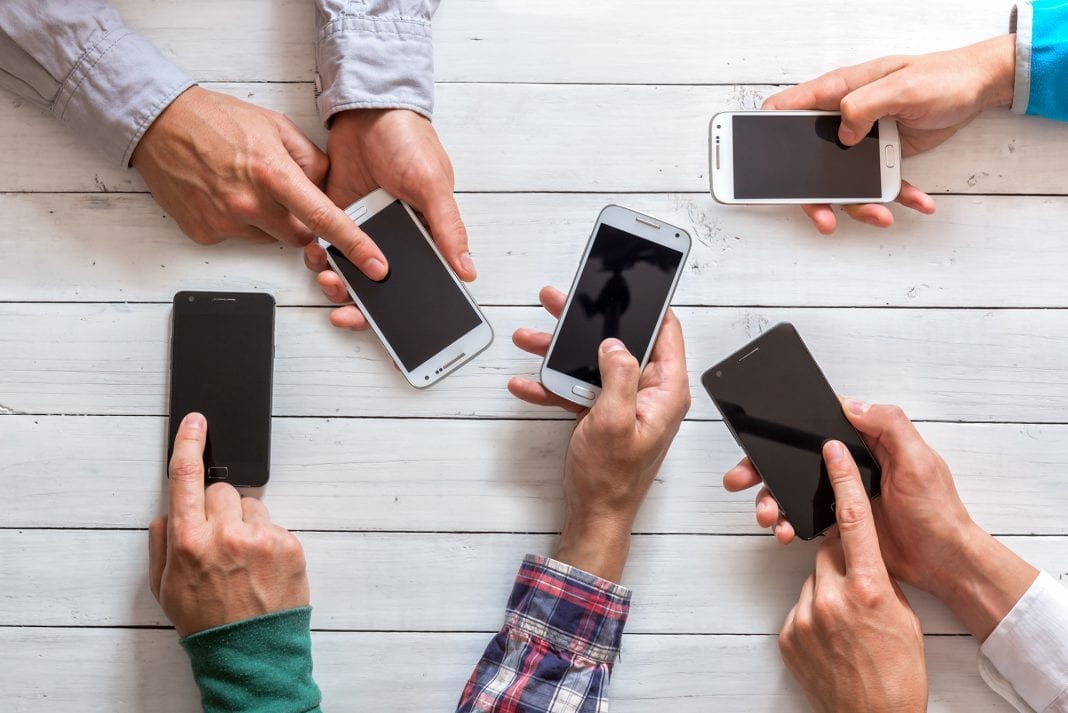 Mobile phones in friends hand